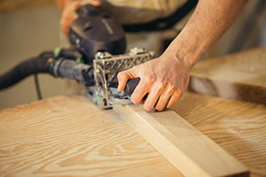 Carpenter planing timber in light workshop